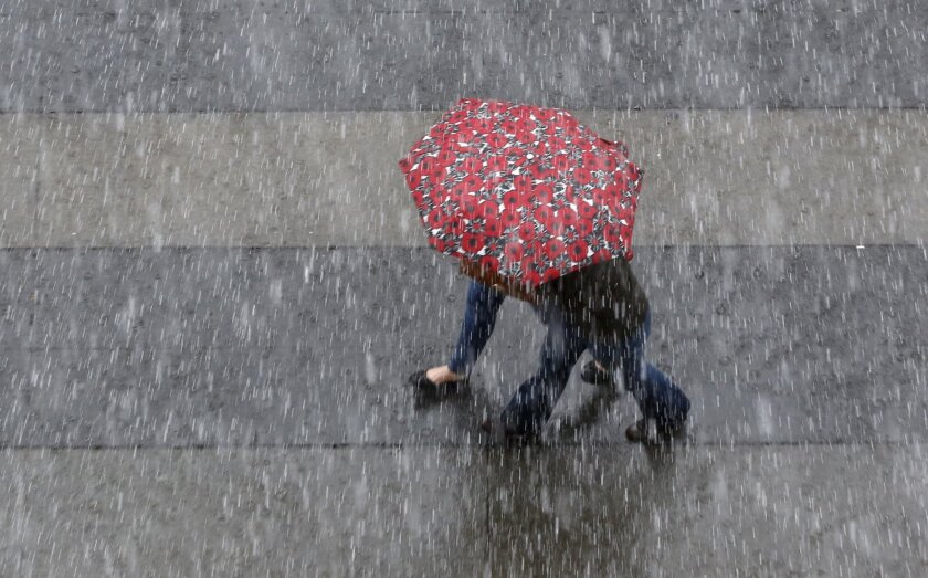 An umbrella is shared as rain pelts downtown Sacramento, Calif., Friday, March 4, 2016. The first of a series of storms swept through Northern California bringing much needed rain to the Central Valley and snow in the mountains.