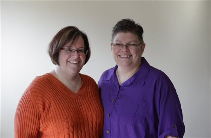 April DeBoer, left, and Jayne Rowse, and pose at their home in Hazel Park, Tuesday, March 5, 2013. The lesbian couple's desire to adopt each other's children has grown into a potentially ground-breaking challenge to Michigan's ban on same-sex marriage. The two Detroit-area nurses filed a lawsuit to try to overturn restrictions on adoption by same-sex partners. But at the judge's invitation, the case has taken an extraordinary turn and now will test the legality of a 2004 constitutional a