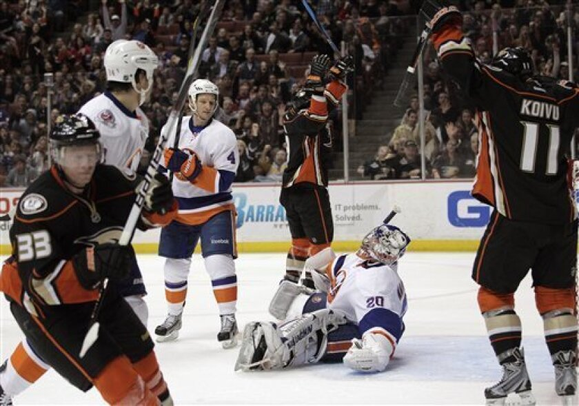 New York Islanders goalie Evgeni Nabokov, bottom center, of Kazakhstan, sits on the ice as the Anaheim Ducks celebrate a goal by Bobby Ryan, background center, during the second period of an NHL hockey game in Anaheim, Calif., Friday, Jan. 6, 2012. (AP Photo/Jae C. Hong)