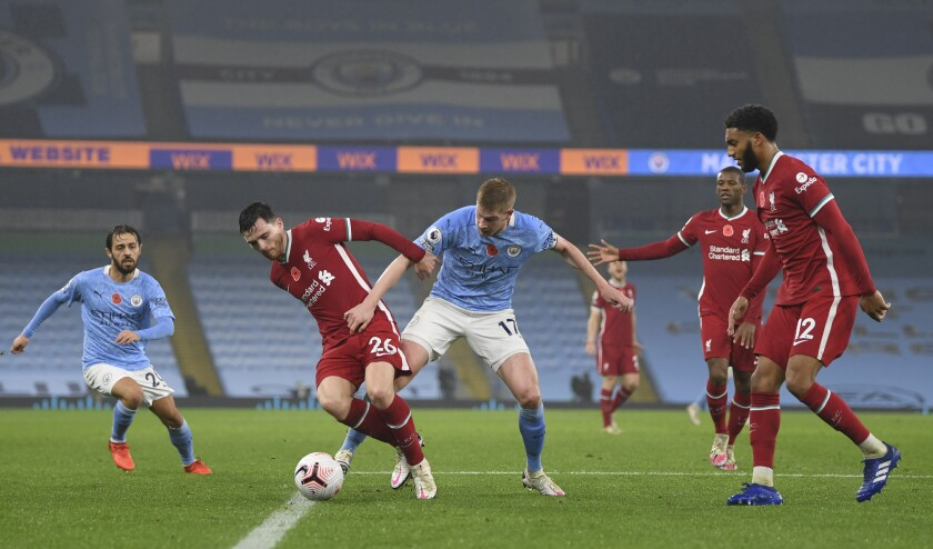 Manchester City's Bernardo Silva, left, and Manchester City's Kevin De Bruyne challenge Liverpool's Andrew Robertson during the English Premier League soccer match between Manchester City and Liverpool at the Etihad stadium in Manchester, England, Sunday, Nov. 8, 2020. (Shaun Botterill/Pool via AP)