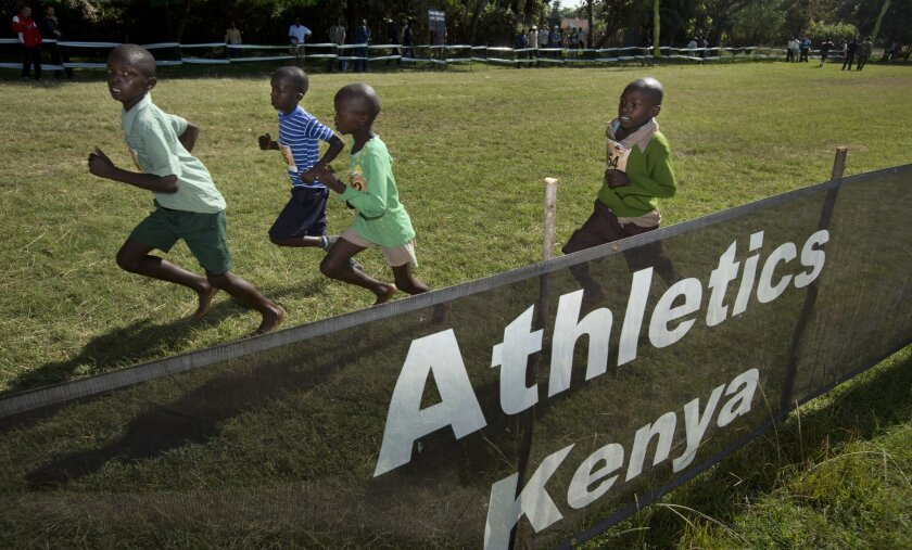 In this photo taken Sunday, Jan. 31, 2016, junior athletes run past a sign for Athletics Kenya at the Discovery cross country races in Eldoret, western Kenya.  Two Kenyan athletes, Joy Sakari and Francisca Koki Manunga, who are both serving a four-year ban for doping at the 2015 world championships