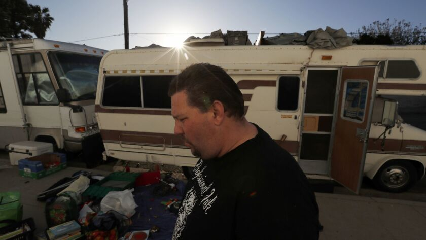 Vincent Neill sorts through personal belongings outside a motorhome parked in an industrial area of Chatsworth where he lives with his family.