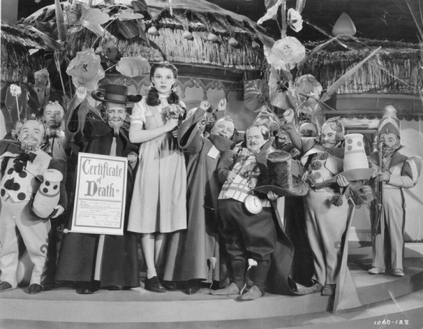 """Munchkin coroner Meinhardt Raabe, third from left, holds the death certificate for the Wicked Witch of the East, who he proclaimed was """"really most sincerely dead."""""""