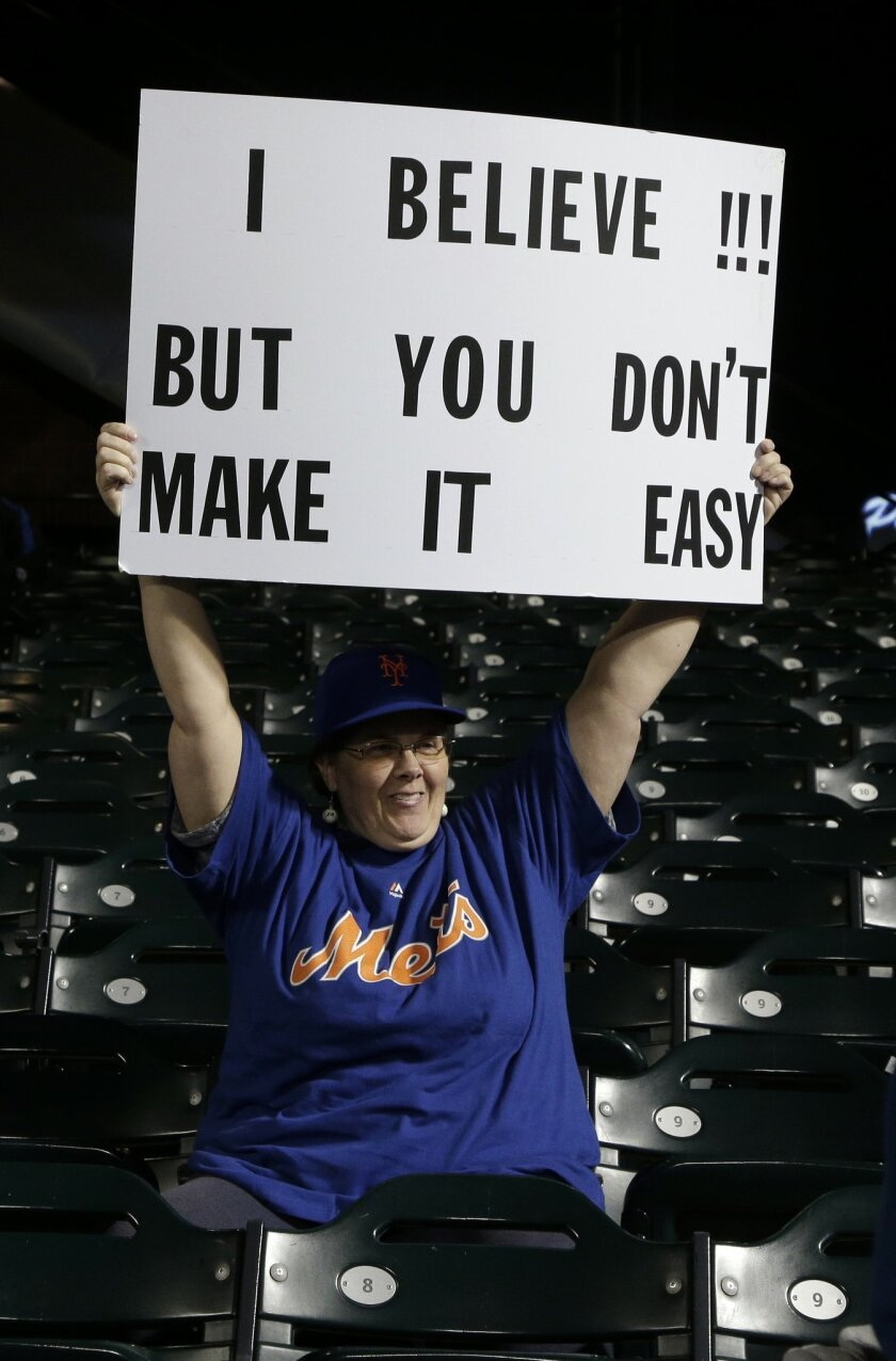 A fan holds up a sign before Game 5 of the Major League Baseball World Series between the New York Mets and Kansas City Royals Sunday, Nov. 1, 2015, in New York. (AP Photo/Charlie Riedel)