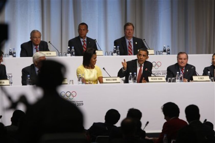 U.S. President Barack Obama, flanked by first lady Michelle Obama, and Chicago Mayor Richard M. Daley, gestures during the USOC's pitch for Chicago to host the 2016 Summer Olympics, Friday, Oct. 2, 2009, at the 121st International Olympic Committee Session in Copenhagen, Denmark. (AP Photo/Gerald Herbert)