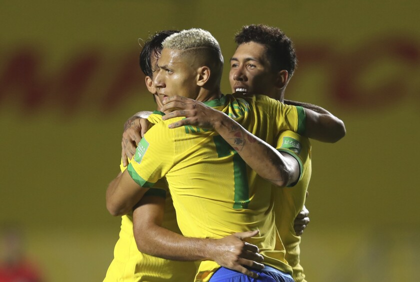 Brazil's Roberto Firmino, right, celebrates with teammates after scoring his side's opening goal against Venezuela during a qualifying soccer match for the FIFA World Cup Qatar 2022 in Sao Paulo, Brazil, Friday, Nov.13, 2020. (Fernando Bizerra/Pool via AP)