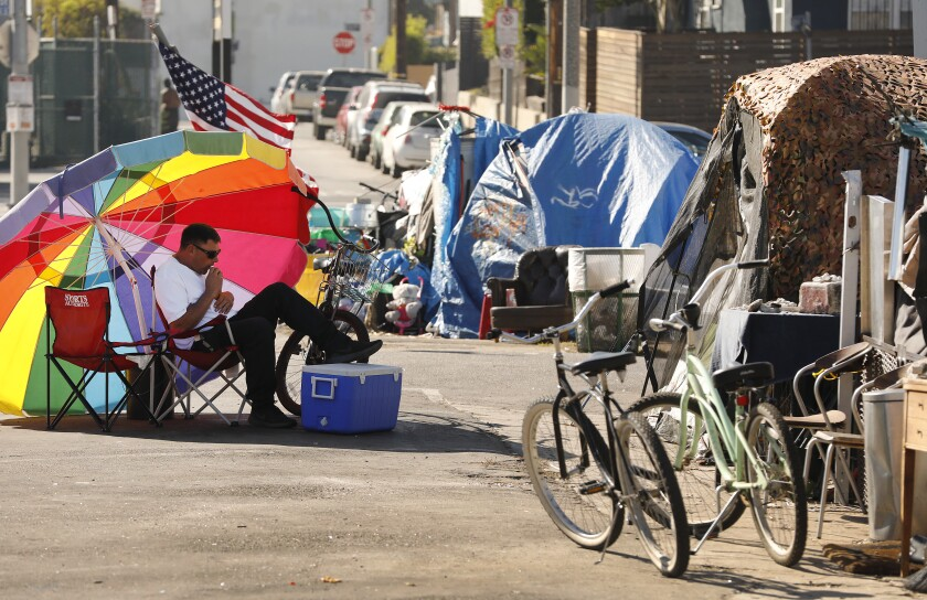 Richard Thompson sits in the shade of his umbrella in a Venice parking lot.