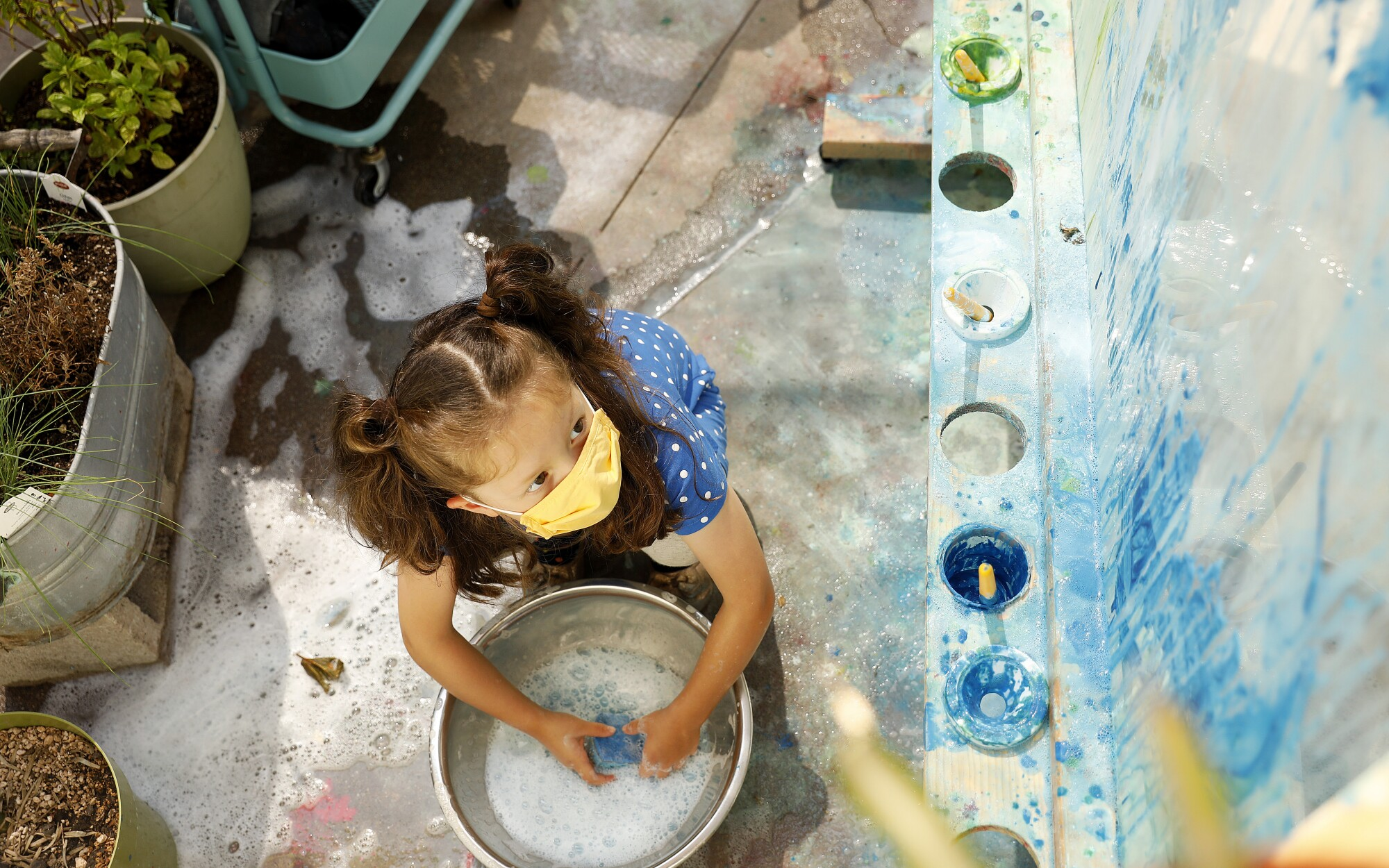 A child wears a mask while painting at Voyages Preschool in Los Angeles.
