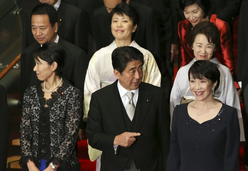 Japan's Prime Minister Shinzo Abe, front row center, and his new Cabinet members pose for a group photo following the first Cabinet meeting at the prime minister's official residence in Tokyo Wednesday, Sept. 3, 2014. The ministers from right in front row, are Internal Affairs Minister Sanae Takaichi, Abe, Trade Minister Yuko Obuchi, from right in second row, Minister in charge of Japanese Abducted by North Korea Eriko Yamatani, Minister in charge of Promoting Women Haruko Arimura, Minister in charge of Economic Revitalization Akira Amari. At right top is Justice Minister Midori Matsushima. (AP Photo/Eugene Hoshiko)