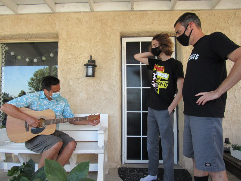 Grossmont High teacher Jeremy Cooke plays a guitar donated to him by Matt Rhea (right) and his son, Spencer Rhea of La Mesa.