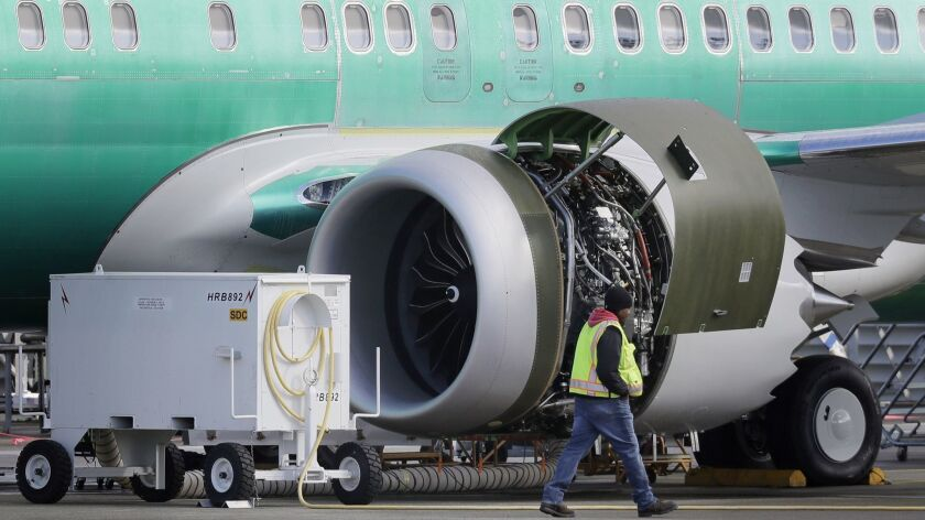 FILE- In this March 13, 2019, file photo a worker walks past an engine on a Boeing 737 MAX 8 airplan