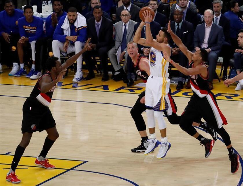 El jugador de los Warriors Stephen Curry (2d) trata de encestar ante los Trail Blazers durante el partido. EFE