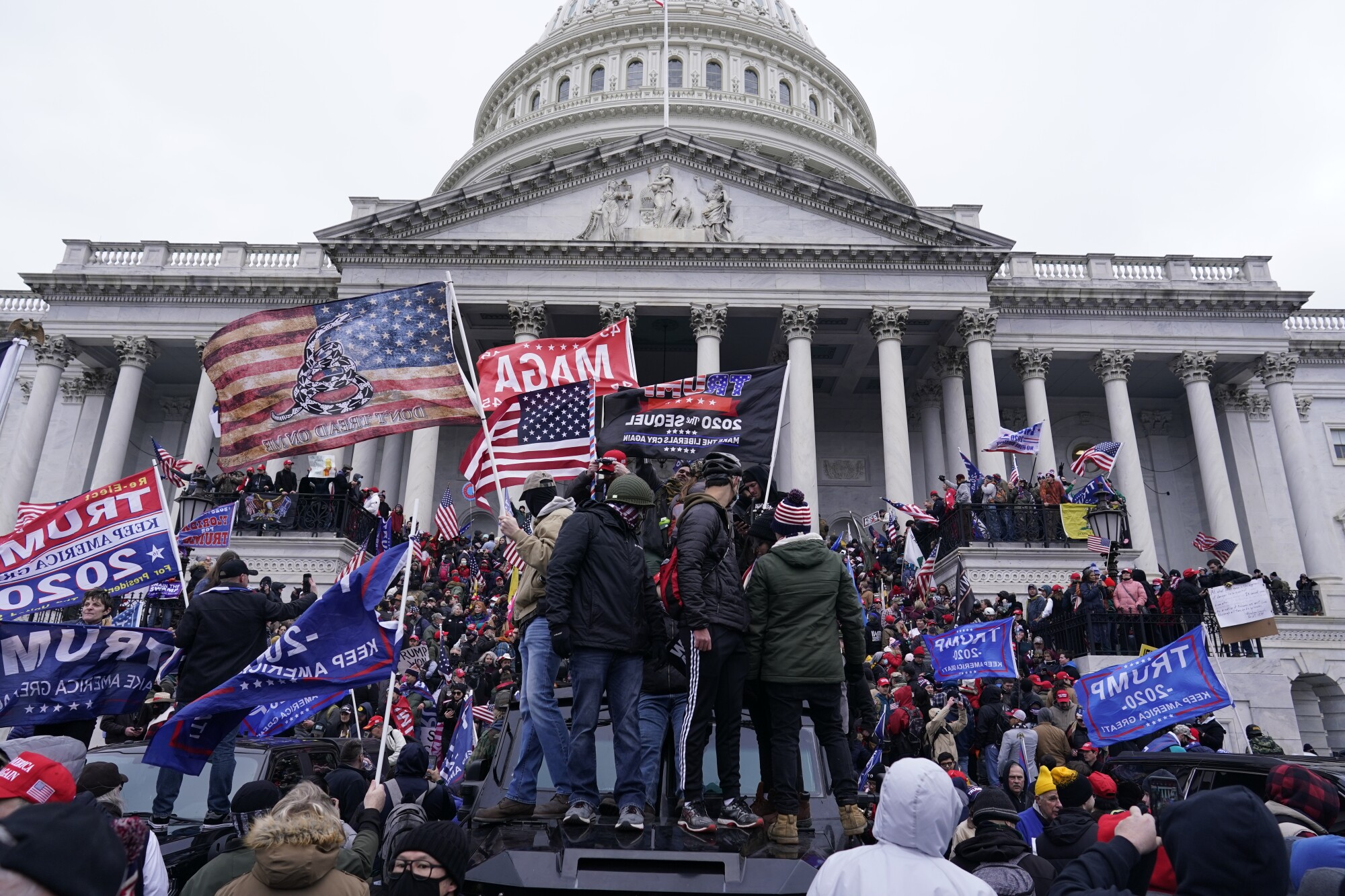 A crowd of people with Trump 2020 and MAGA flags stand on an armored police vehicle and the Capitol steps
