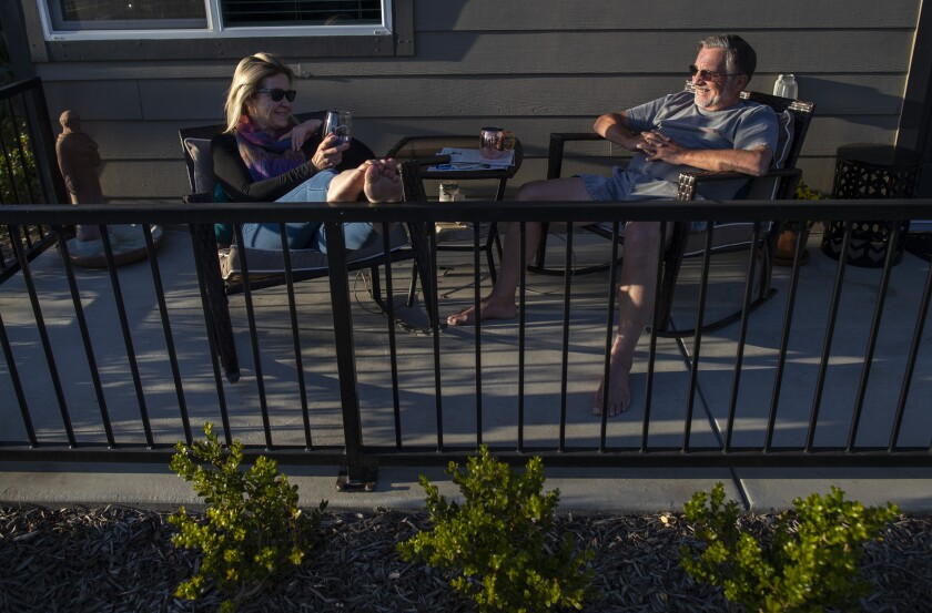 Bree McDowel, left, and Bill Van Heusen, right, enjoy the sunset from their patio at The Row in Fresno.
