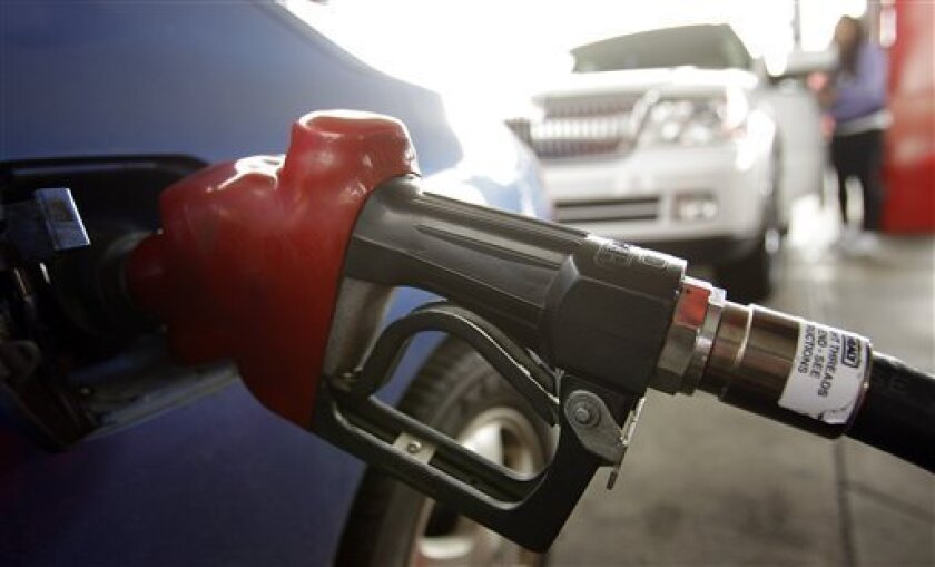 FILE - In this file photo taken March 8, 2011, gasoline is dispensed at a station in Oakland, Calif. Gasoline pump prices across the U.S. fell slightly Tuesday, March 15, for the first time in nearly a month to a national average of $3.556 per gallon. Prices are still higher than ever for this time of year. (AP Photo/Ben Margot, file)