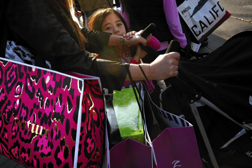 Kira Nishihira, 5, does last-minute shopping with her family at the Third Street Promenade. Nearly 8 in 10 consumers in one survey said they plan to shop year-end sales.