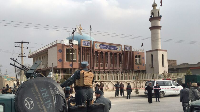 Afghan security officers stand guard in front of a Shiite mosque after a suicide bomb blast killed dozens in Kabul on Monday.