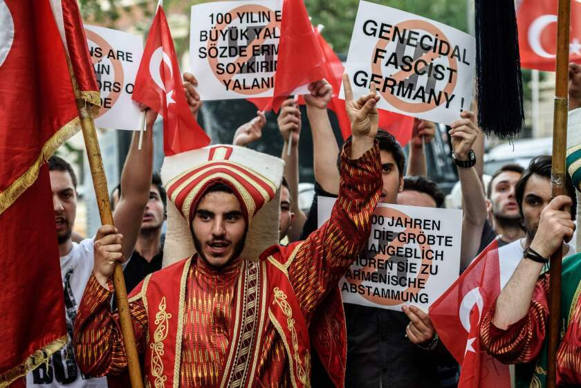 "Turkish nationalist protesters flash the nationalist organization's ""grey wolf"" sign and hold placards during a protest against Germany on June 2, 2016 in front of the Germany consulate in Istanbul after German parliament labeled the World War I massacre of Armenians by Ottoman forces as genocide."