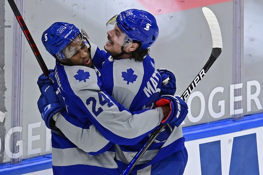 Toronto Maple Leafs right wing Wayne Simmonds (24) celebrates his goal against the Vancouver Canucks with teammate Auston Matthews (34) during first-period NHL hockey game action in Toronto, Saturday, Feb. 6, 2021. (Frank Gunn/The Canadian Press via AP)