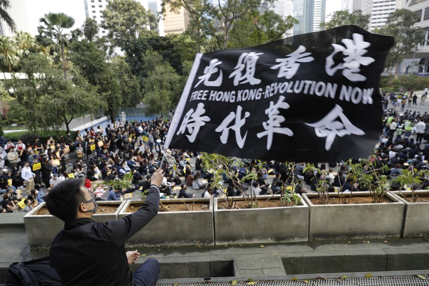 A pro-democracy supporter waves a flag during a rally by the advertising industry in Hong Kong on Monday. Thousands of people took to Hong Kong's streets Sunday in a new wave of protests, but police fired tear gas after some demonstrators hurled bricks and smoke bombs, breaking a rare pause in violence that has persisted during the six-month-long movement.