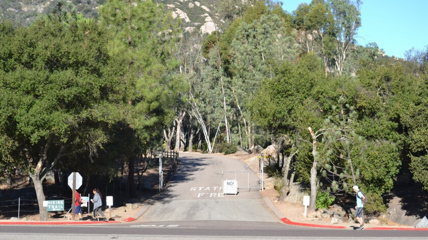 Hikers walk past the freshly red-painted curbs at the entrance to the Mt. Woodson Cal Fire Station a