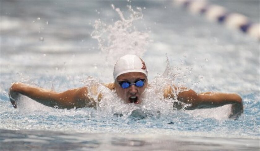 Katinka Hosszu takes a breath on her way to winning the women's 100-meter butterfly event at the Indianapolis Grand Prix swimming meet in Indianapolis, Saturday, March 31, 2012.  (AP Photo/Michael Conroy)