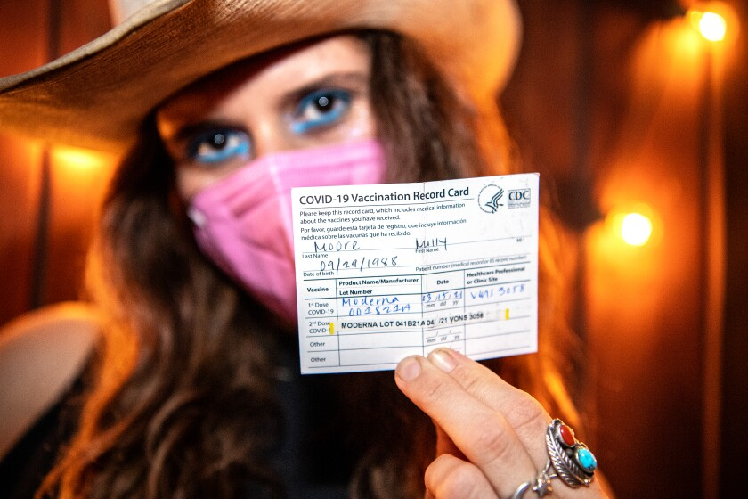 A woman in a cowboy hat and mask holds up a COVID vaccination card