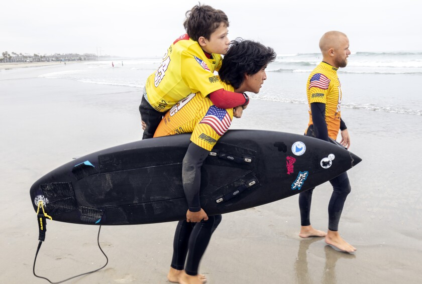 Surfer Hunter Pochop, 14, is carried to the water by Adam Calderon before the start of his prone assist contest at the USA Surfing Adaptive Surfing Championship at Oceanside Harbor North Jetty.