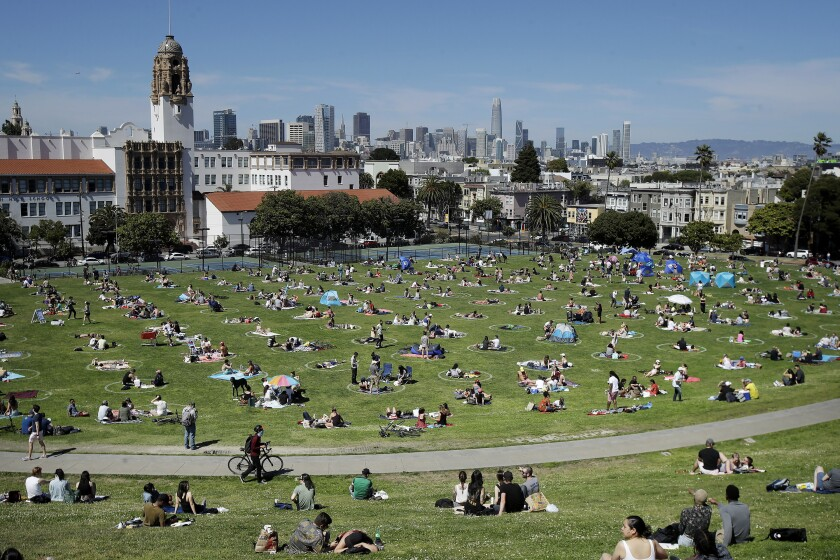 Visitors sit inside circles designed to help prevent the spread of the coronavirus at Dolores Park in San Francisco.