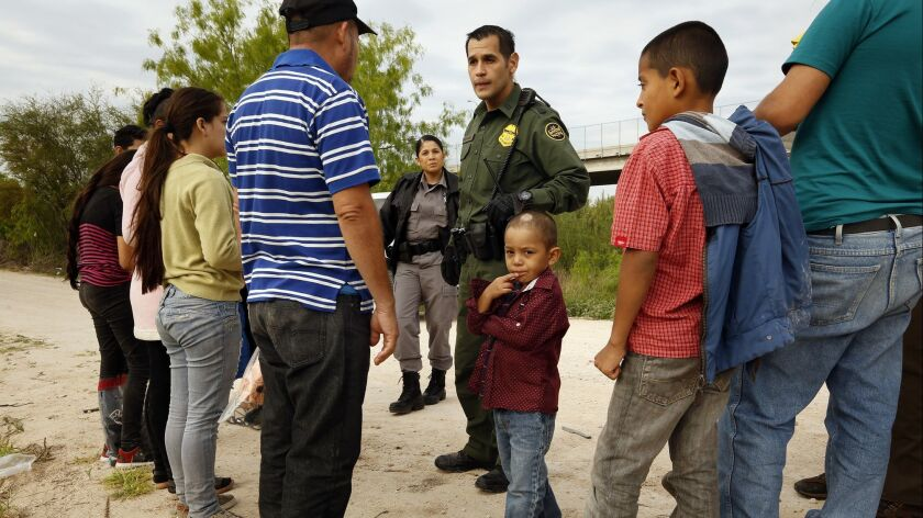 Ely Fernandez of Honduras is questioned by Border Patrol Agent Robert Rodriguez after being detained for crossing the border illegally in March with his 5-year-old son, Bryan, center.