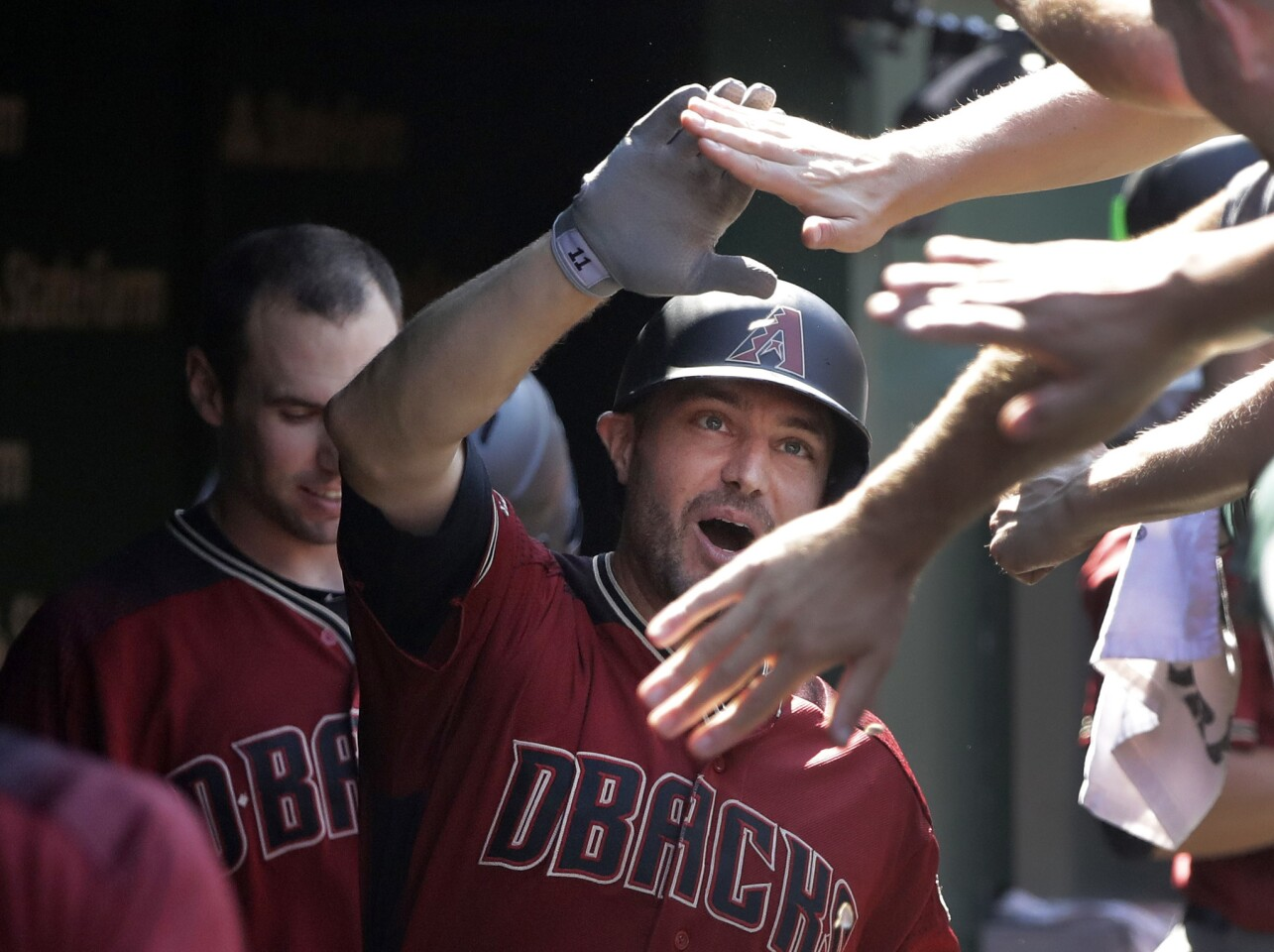 Arizona Diamondbacks' A.J. Pollock celebrates his home run off Chicago Cubs starting pitcher Jon Lester in the dugout during the seventh inning of a baseball game Wednesday, July 25, 2018, in Chicago. (AP Photo/Charles Rex Arbogast)