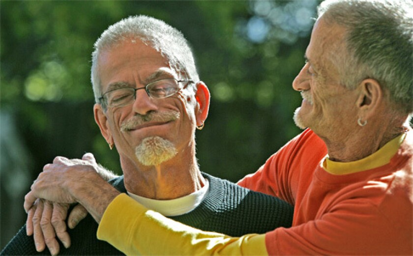 'WE'RE STILL HERE': Dennis Golay, 60, left, and Larry Gibson, 63, in the garden of their Palm Springs home. Both men tested positive for HIV in the days before antiretroviral drugs.