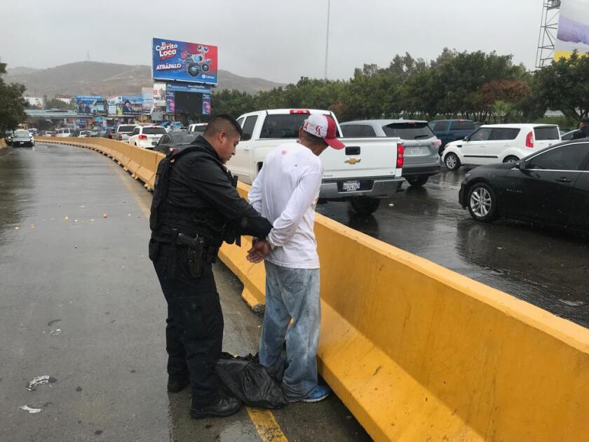 Tijuana police officer arrests man on suspicion of showing aggression against drivers waiting in Sentri lane at the San Ysidro border.