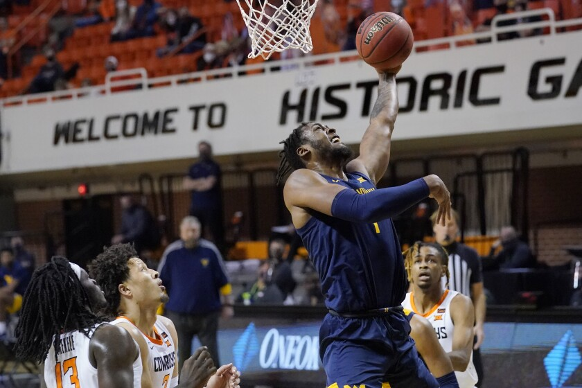 West Virginia forward Derek Culver, center, shoots in front of Oklahoma State guards Isaac Likekele (13) Cade Cunningham (2) and Rondel Walker, right, in the first half of an NCAA college basketball game Monday, Jan. 4, 2021, in Stillwater, Okla. (AP Photo/Sue Ogrocki)