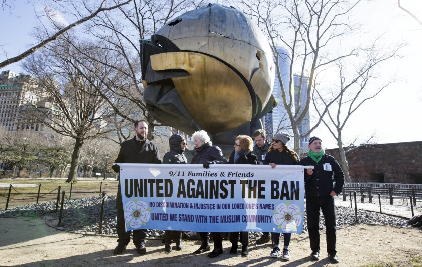 Relatives of those killed in the Sept. 11, 2001, terrorist attacks gather in front of a sculpture that once stood in front of the World Trade Center to show their opposition to President Trump's travel ban.