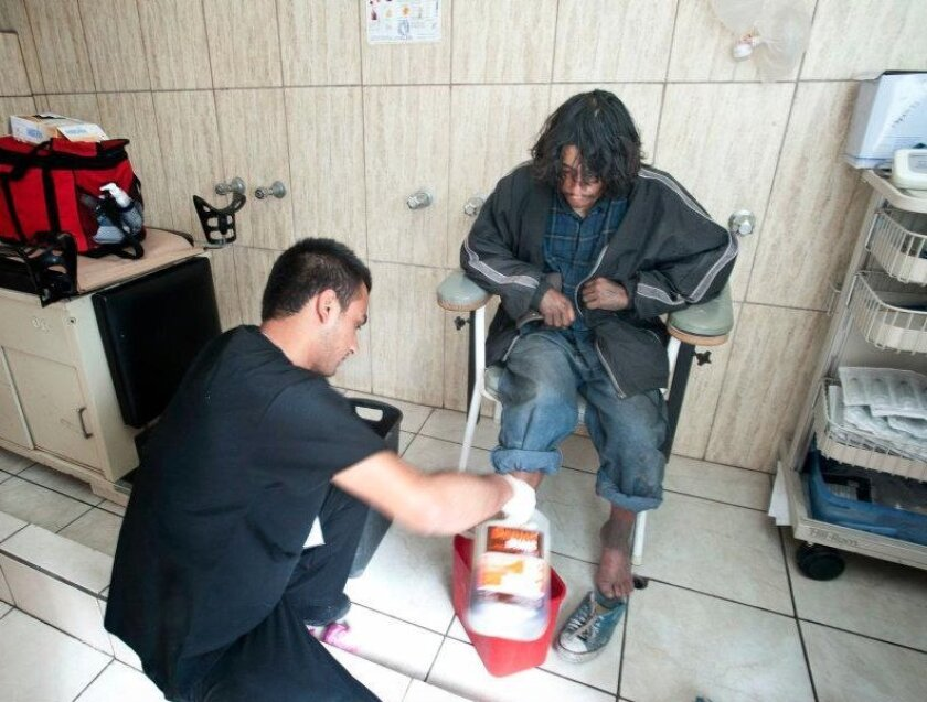 Students from UC San Diego and Autonomous University of Baja California run a free clinic in Tijuana that treats a wide variety of health problems, including HIV and tuberculosis. In this image, a clinic trainee is washing an abscess on a man who lives in the Tijuana River channel.