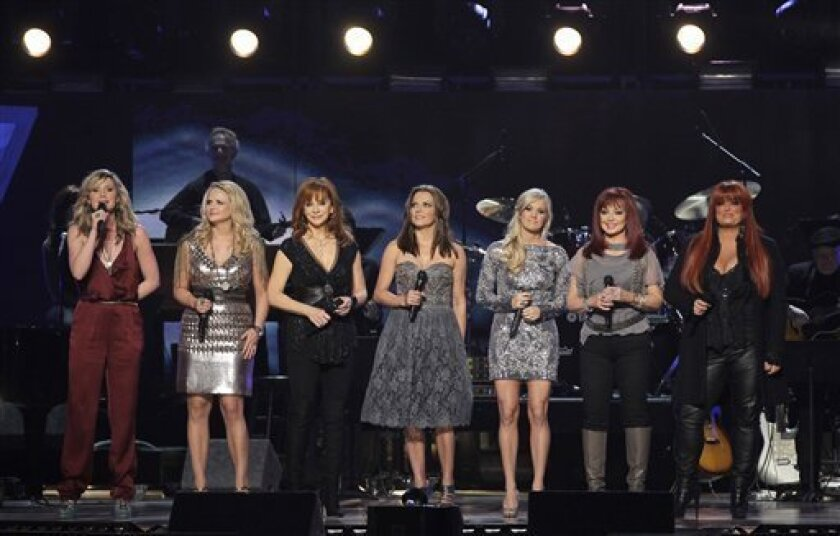 """From left, Jennifer Nettles, Miranda Lambert, Reba McEntire, Martina McBride, Carrie Underwood, Naomi Judd and Wynonna Judd are seen on stage in 2011 at the """"Girls Night Out: Superstar Women of Country"""" concert in Las Vegas."""