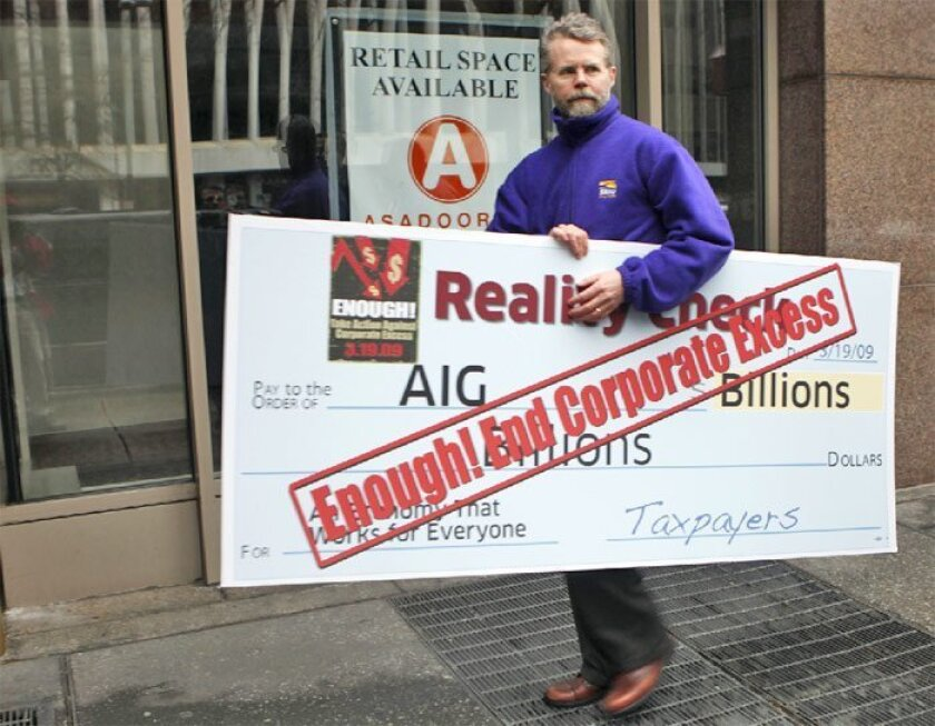 A protester carried a giant novelty check yesterday outside the Washington, D.C., offices of American International  Group after a demonstration in support of banking reform. (Pablo Martinez Monsivais / Associated Press)