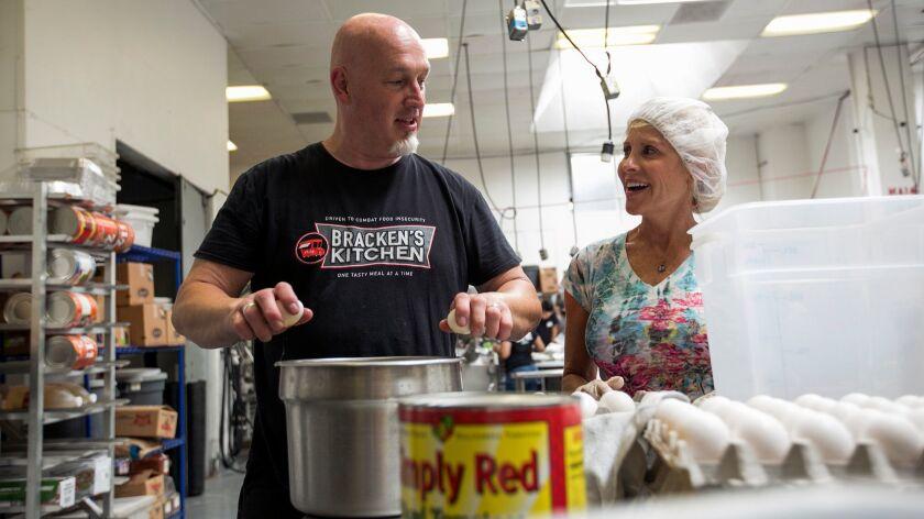 Bill Bracken, founder of Bracken'™s Kitchen, shows volunteer Krista Koch how to crack eggs with one