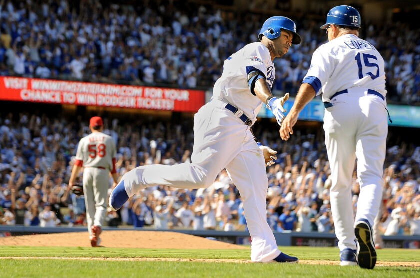 Dodgers left fielder Carl Crawford is congratulated by first base coach Davey Lopes after hitting a home run in the fifth inning of Game 5.