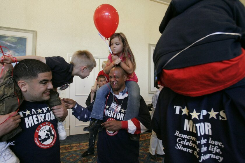 At a camp hosted by the Tragedy Assistance Program for Survivors, or TAPS, mentors play with children who have lost military loved ones to suicide or other causes. / photo by John Gibbins * U-T