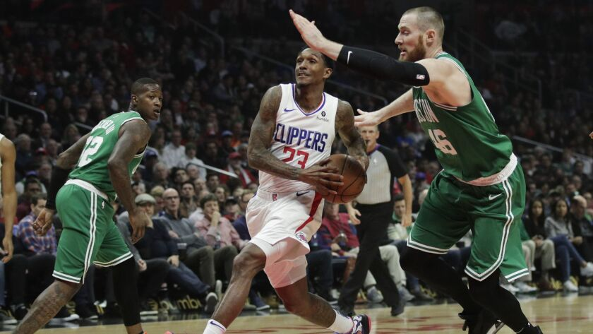 Clippers' Lou Williams, center, drives to the basket while defended by Boston Celtics' Aron Baynes during the first half.