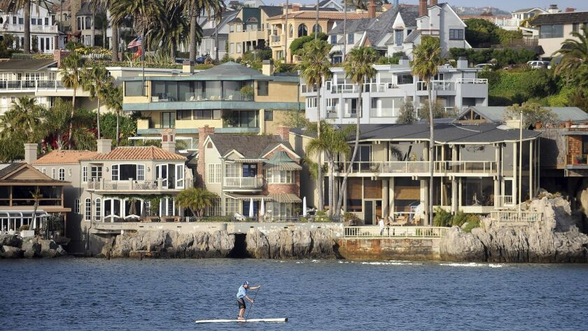 A paddleboard makes his way through the Newport Beach Harbor in Newport Beach, where residents have been complaining about a foul smell in the air.