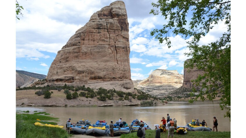 Rafters stretch their legs near Steamboat Rock before hiking up a side canyon to see Native American petroglyphs and caves.