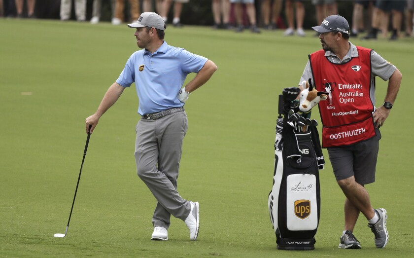 South Africa's Louis Oosthuizen, left, waits to play his second shot on the 6th hole during the second round of the Australian Open golf tournament in Sydney, Friday, Dec. 6, 2019. (AP Photo/Rick Rycroft)