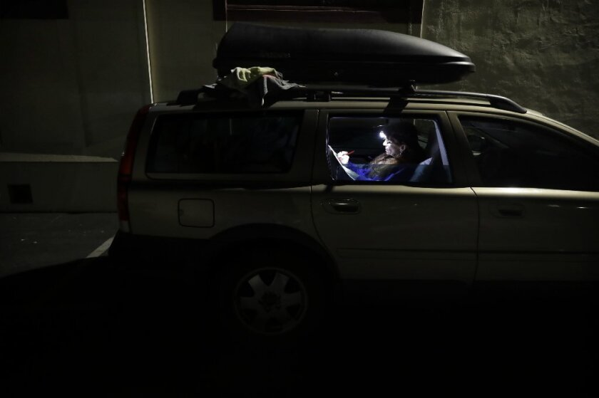 Ellen James-Penney, a lecturer at San Jose State University, prepares a lesson for the class she teaches, inside a station wagon where she sleeps at Grace Baptist Church on Tuesday, Oct. 10, 2017, in San Jose, Calif.
