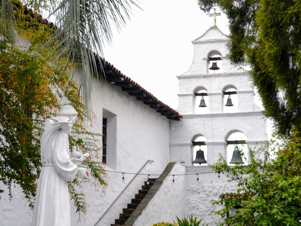 Las campanas de la misión San Diego de Alcalá. La campana en la parte inferior izquierda es Mater Dolorosa, Nuestra Señora de los Dolores, de 1,200 libras, la más pesada de las cinco. Fue refundido en la década de 1890. Suena a diario. La estatua a la izquierda es San Francisco.