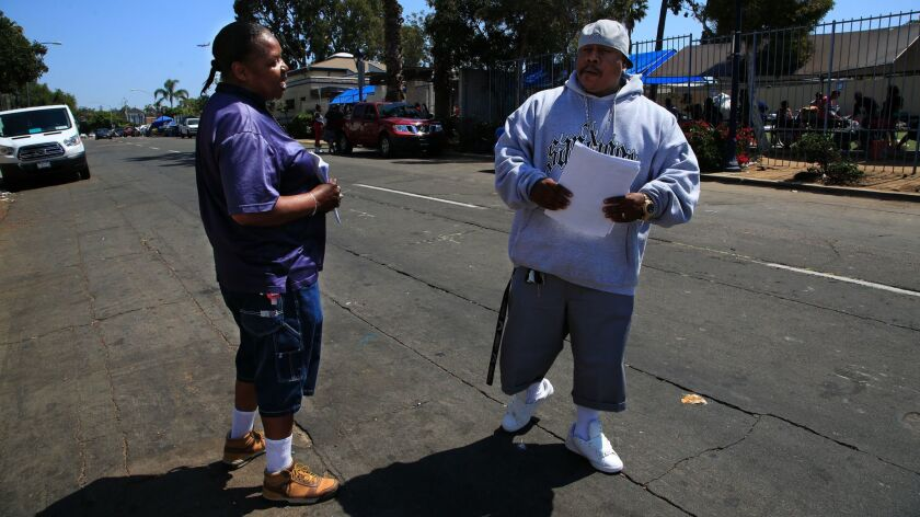 "Outreach workers from The Alpha Project, Ola Jackson and Quarlo ""Q"" McSwain walk the streets passing"