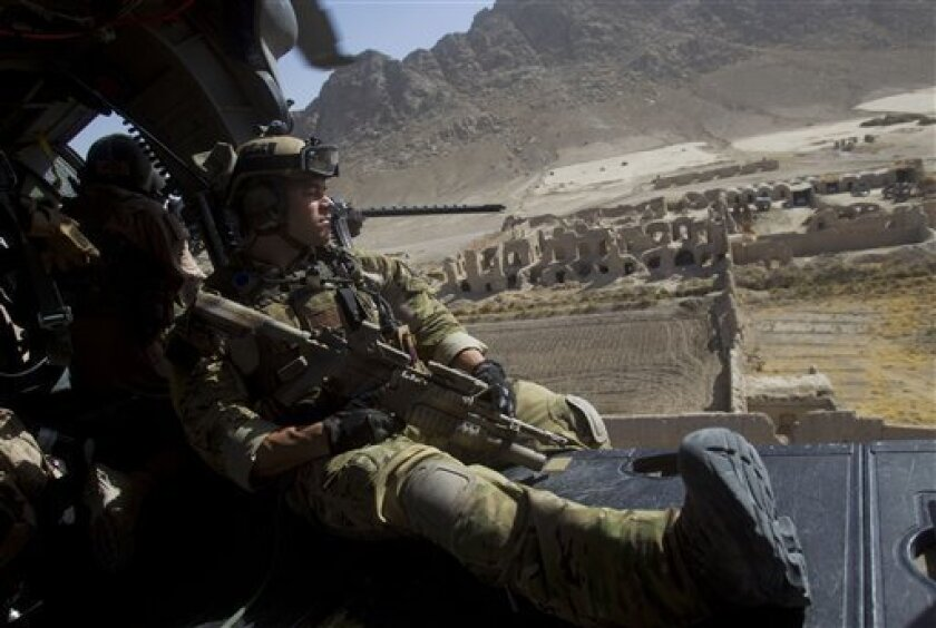 Air Force pararescueman SSgt Mark Bedell of the 46th Expeditionary Rescue Squadron looks out of the open door of a HH-60G Pave Hawk helicopter as they fly low over a village in Afghanistan's Kandahar province on Saturday Oct. 9, 2010. (AP Photo/David Guttenfelder)
