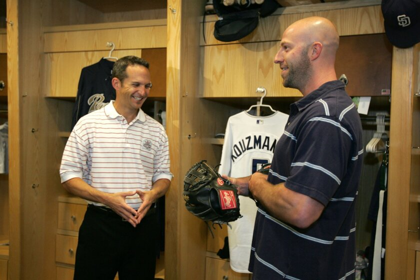 Padres' Kevin Kouzmanoff, who set an NL fielding record with a .990 percentage, hands over his glove to Hall of Fame President Jeff Idelson (left).